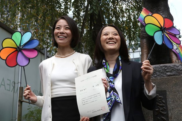 "Japanese gay couple Hiroko Masuhara (R) and Koyuki Higashi display a certification paper of ""partnership"" issued by the Shibuya ward office after they received it in Tokyo on November 5, 2015. While the certificates are not be legally binding, the district hoped they would encourage hospitals and landlords to ensure same-sex couples receive similar treatment to married people. AFP PHOTO / Yoshikazu TSUNO        (Photo credit should read YOSHIKAZU TSUNO/AFP/Getty Images)"